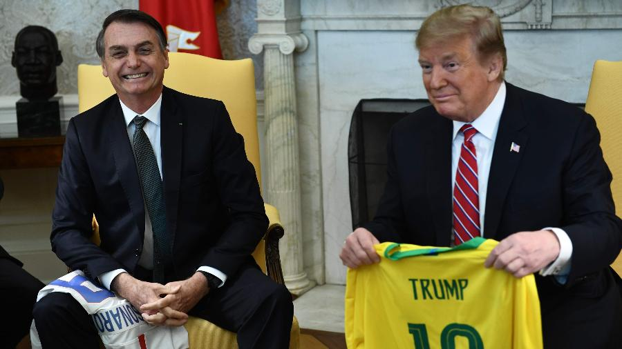 19.mar.2019 - Presidente dos EUA Donald Trump segura uma camiseta do Brasil em seu encontro com Bolsonaro - Brendan Smialowski / AFP