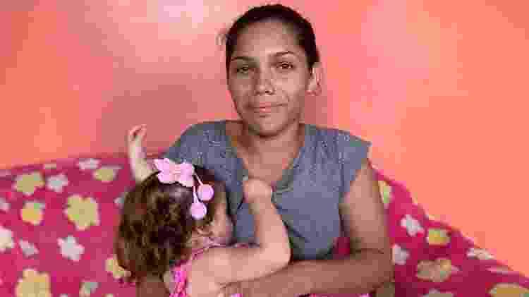 Carol da Silva e Silva (à direita na janela), moradora de Manacapuru cuja filha bebê foi infectada e correu risco de morrer - Maria Fernanda Ribeiro/UOL