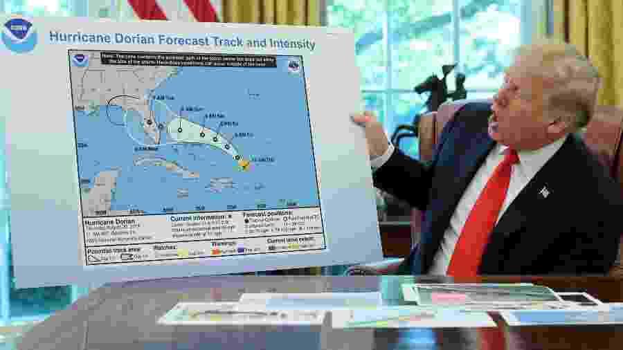 Donald Trump expõe um cartaz com uma linha preta junto ao desenho oficial da trajetória do furacão Dorian - JONATHAN ERNST / REUTERS