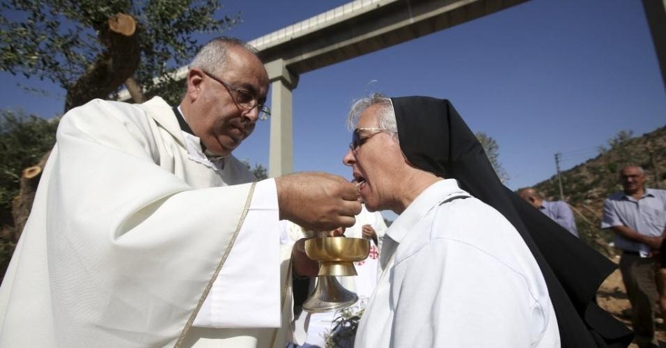 21.ago.2015 - Cristãos palestinos celebram uma missa de protesto em um território que Israel quer confiscar para a expansão de sua barreira de separação, perto da cidade de Biet Jala, próxima a Belém, na Cisjordânia
