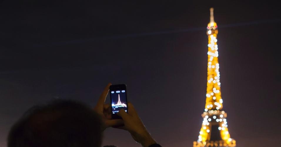 10.mar.2016 - Turistas fotografam a torre Eiffel e seu show de luzes com telefones celulares. A cada hora durante a noite, o ícone parisiense cintila por alguns minutos