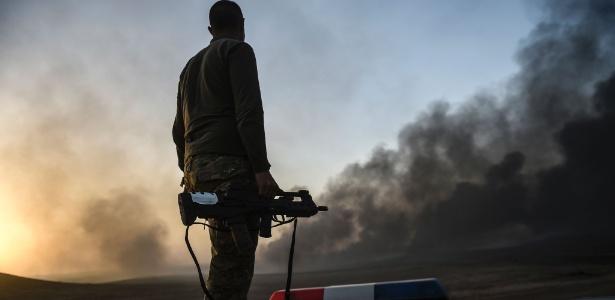 Membro da força de segurança do Iraque observa fumaça na região de Qayyarah, cerca de 60 km a sul de Mosul