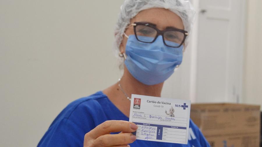 Profissional de saúde de hospital de João Pessoa (PB) mostra cartão de vacina para covid-19 preenchido - Ivomar Gomes/ Prefeitura de João Pessoa