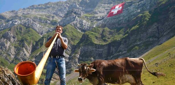 Homem toca espécie de berrante gigante ao lado da bandeira nacional e de uma vaca tradicional durante as comemorações do Dia Nacional da Suíça