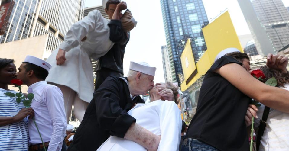 14.ago.2015 - Casais se beijam em frente a uma escultura que retrata o famoso beijo registrado pelo fotógrafo Alfred Eisenstaedt na Times Square, em Nova York, no dia em que a grande guerra teve seu fim, para celebrar os 70 anos da icônica fotografia
