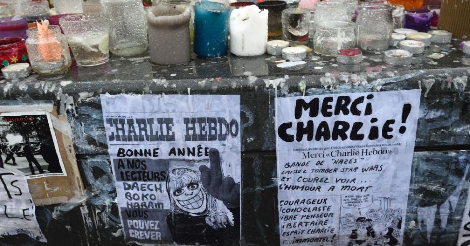 """7.jan.2015 - Cartazes e velas são postos em memorial improvisado na place de la Republique, em Paris, um ano depois do atentado ao semanário satírico francês Charlie Hebdo. Em um dos cartazes lê-se """"Feliz Ano-Novo para os nossos leitores. Estado Islâmico e Boko Haram vão para o inferno"""". A França realiza cerimônias oficiais hoje para lembrar o ataque jihadista que matou 12 pessoas, entre cartunistas e outros funcionários na redação do jornal"""