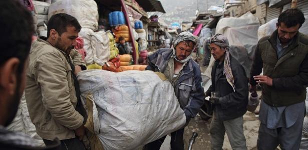 Funcionários de Ramazan carregam fardo de roupas para um varejista em Cabul