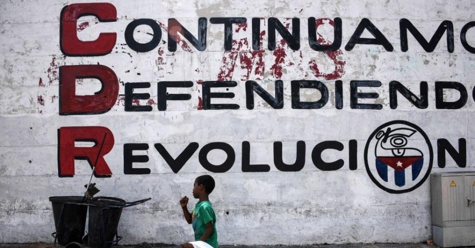 """19.mar.2016 - Criança passa por muro em Havana (Cuba) onde se lê """"Continuamos Defendendo a Revolução"""", em alusão à sigla CDR, dos Comitês de Defesa da Revolução cubana. Neste domingo, o presidente dos Estados Unidos, Barack Obama, embarca para a ilha, onde ficará por dois dias em visita oficial, em mais uma etapa da retomada de relações entre os dois países. Esta será a primeira visita de um presidente norte-americano desde 1928"""