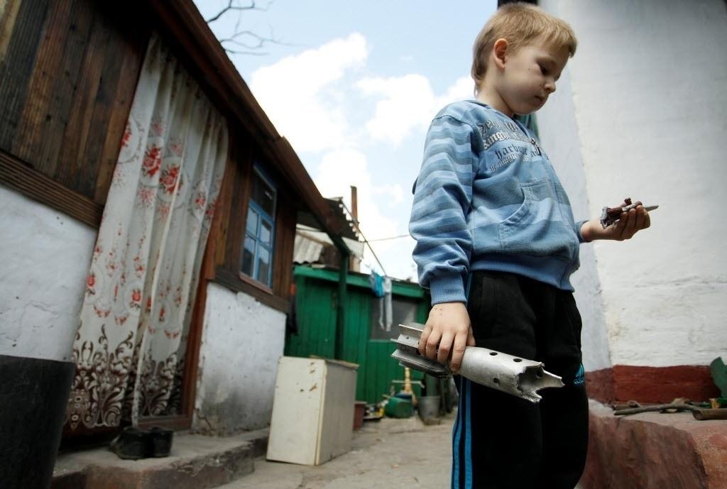 24.mai.2016 - Um menino segura os restos de um projétil encontrado nos escombros de um prédio residencial destruído pela explosão da bomba, na aldeia de Staromikhailovka, fora de Donetsk, na Ucrânia