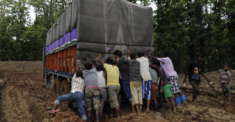 5.jul.2016 - Indianos empurram caminhão que ficou atolado em estrada de terra próximo à cidade de Khasiapunji. A região vem sofrendo com a intensas chuvas causadas pelo período de monções