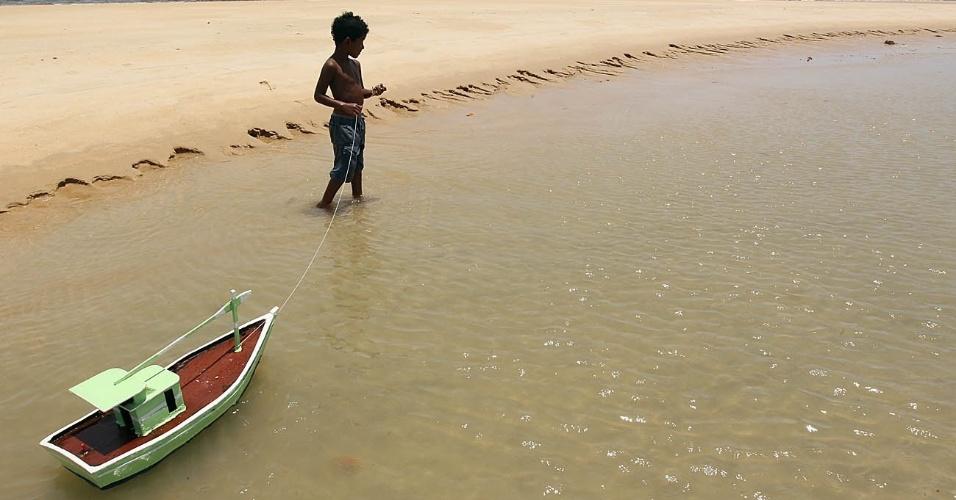 27.dez.2016 - Na Bahia, o menino brinca com o barquinho na praia de Ponta do Corumbau, em Prado, para se refrescar