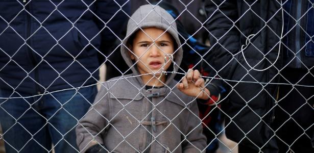 Criança iraquiana que fugiu do Estado Islâmico em Mossul observa da cerca do campo de refugiados Khazer, no Iraque