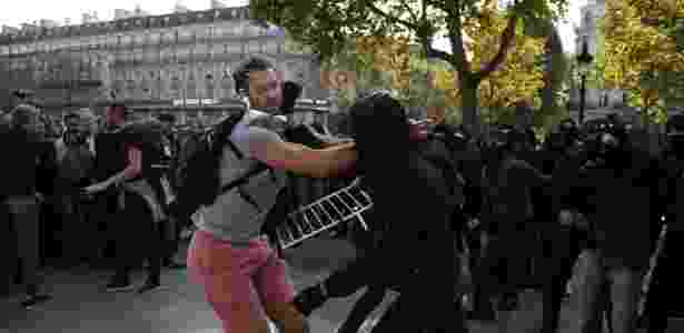 Manifestante tenta impedir grupo de mascarados de invadir um palanque durante protesto convocado por opositores das reformas trabalhistas propostas pelo governo francês - Zakaria Abdelkafi/AFP