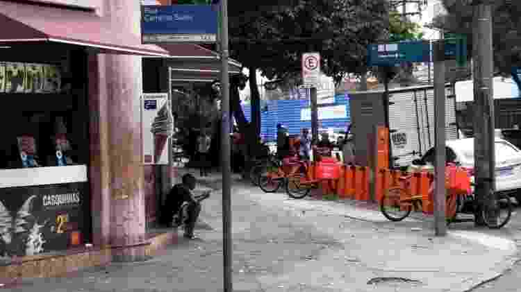Sentados na calçada, entregadores aguardam pedidos perto de lanchonete na Tijuca - Igor Mello/ UOL - Igor Mello/ UOL