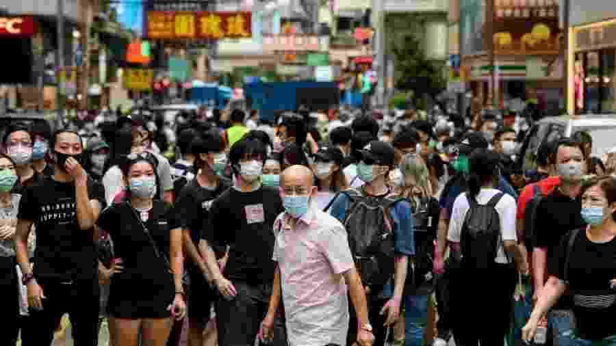 """27.mai.2020 - Manifestantes olham na direção de um grupo de policiais de choque no bairro de Mongkok, em Hong Kong, enquanto a cidade debate uma lei que proíbe """"insultar"""" o hino nacional. A polícia usou gás de pimenta e prendeu centenas de pessoas que protestavam - Anthony Wallace/AFP"""