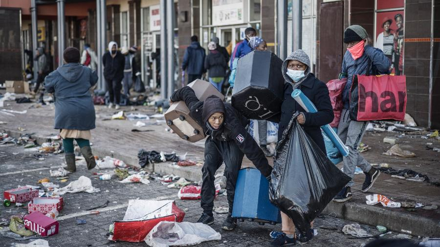 14.jul.2021 - Saqueadores levam alguns itens que sobraram em um shopping vandalizado na cidade de Vosloorus, na África do Sul. - MARCO LONGARI/AFP