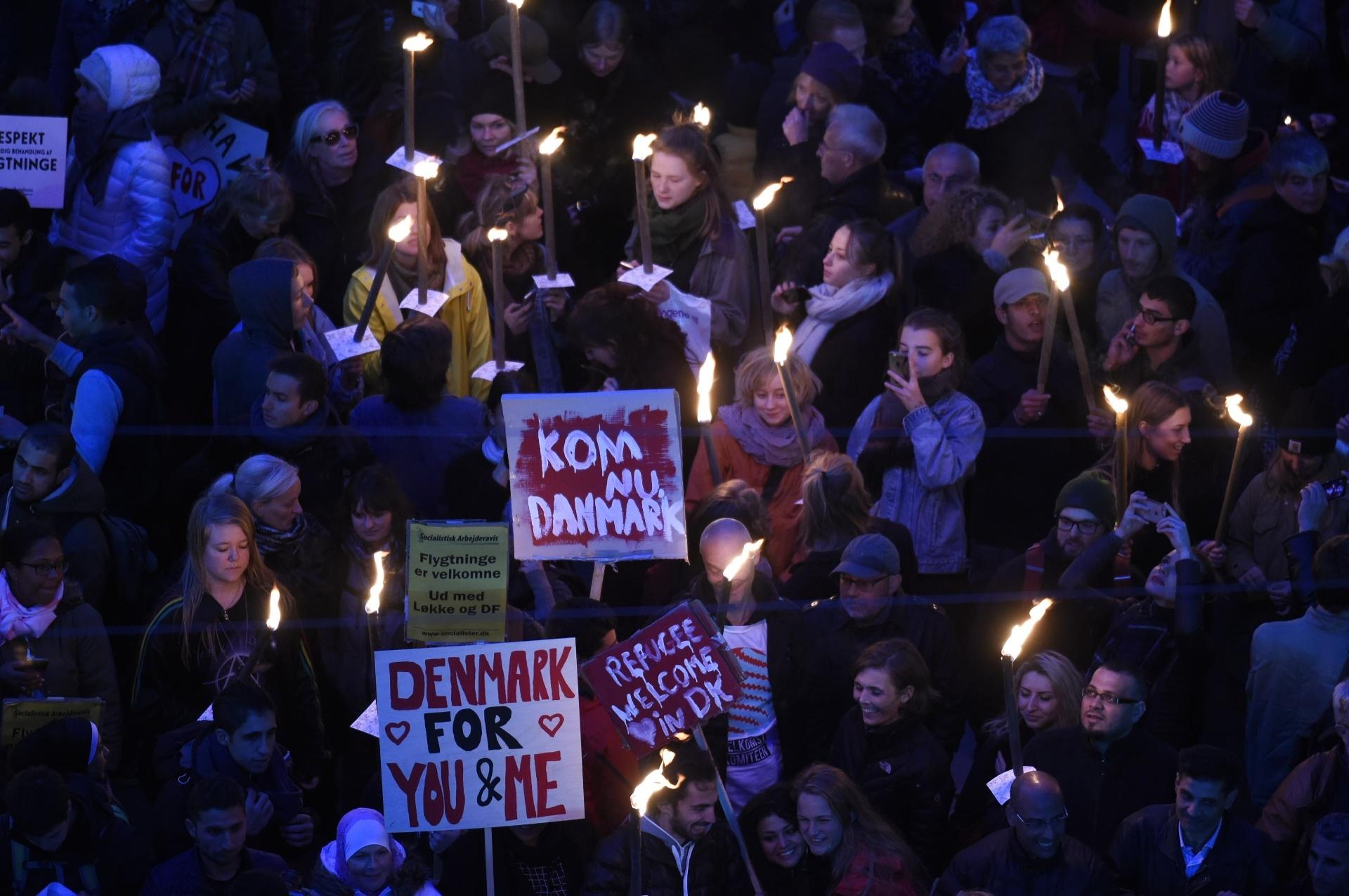 6.out.2015 - Diante do Parlamento dinamarquês, moradores da capital do país, Copenhague, se manifestam a favor da recepção de refugiados. A Dinamarca endureceu recentemente as regras para pedidos de asilo. Segundo o FMI, a chegada maciça de refugiados pode pesar no orçamento europeu, mas impulsionará o crescimento no longo prazo