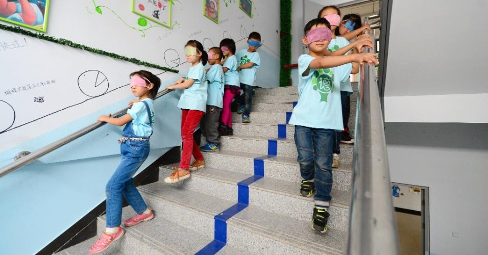 14.out.2015 - Crianças participam de atividade com os olhos vendados em uma escola primária de Xingtai, província de Hebei, norte da China. A ideia é que os alunos experimentem um pouco da vida dos deficientes visuais durante a atividade extracurricular