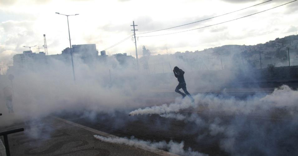 11.nov.2015 - Manifestante palestino tenta se proteger do gás lacrimogêneo disparado por soldados israelenses durante enfrentamentos na cidade de Belém, na Cisjordânia