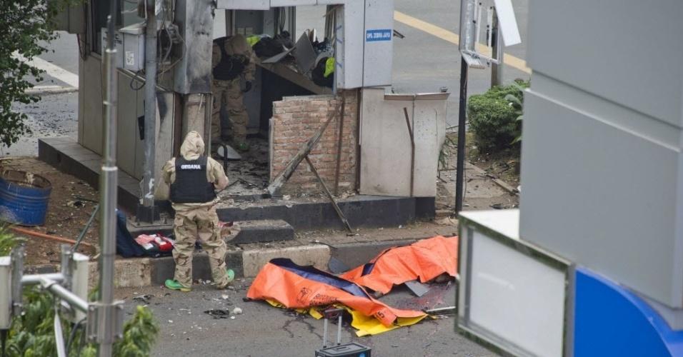 14.jan.2016 - Policiais passam por corpos das vítimas de uma série de explosões que atingiu a região central de Jacarta, na Indonésia.  Dois civis, incluindo um holandês, e cinco criminosos morreram nas explosões e tiroteios segundo o governo da Indonésia