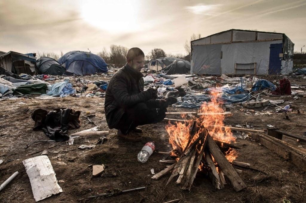 18.jan.2016 - Hemn, um imigrante curdo, se aquece em fogueira em acampamento de refugiados improvisado no porto de Calais, que dá acesso à Inglaterra, na França. O local, apelidado de