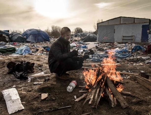 Hemn, imigrante curdo, se aquece em fogueira no acampamento de refugiados improvisado no porto de Calais (França), perto do acesso para a Inglaterra