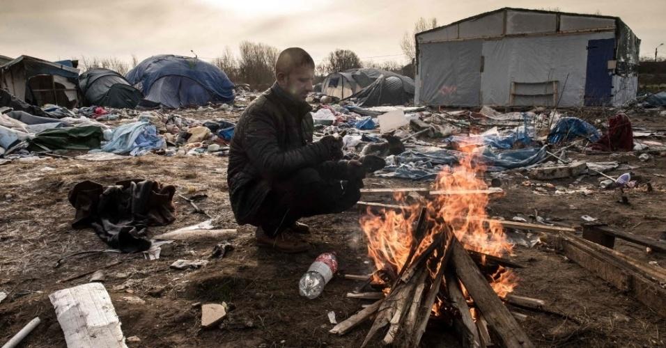 """18.jan.2016 - Hemn, um imigrante curdo, se aquece em fogueira em acampamento de refugiados improvisado no porto de Calais, que dá acesso à Inglaterra, na França. O local, apelidado de """"selva"""" (the jungle, em inglês), está sendo desmontado pelas autoridades francesas, que demolem as tendas e retiram objetos utilizando retroescavadeiras. Os refugiados foram informados que terão apenas alguns dias para limpar centenas de barracos feitos de tábuas de madeira e lona, antes da remoção que será feita no local"""