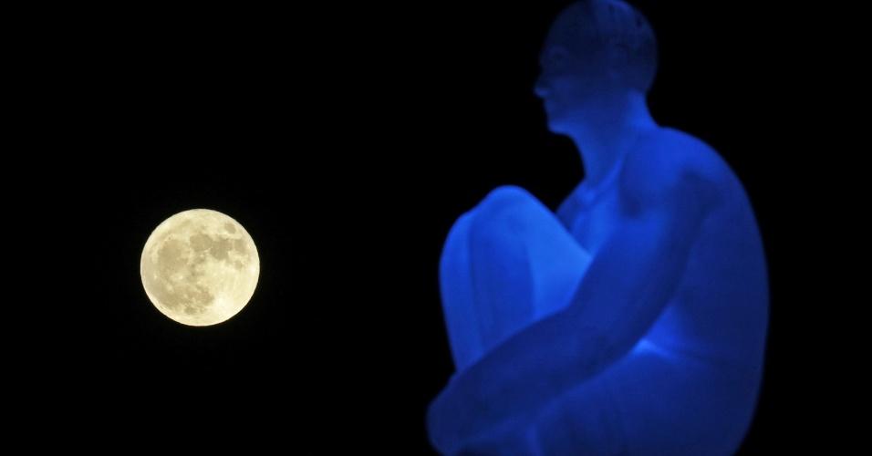 14.nov.2016 - Superlua aparece atrás de uma das sete estátuas do artista espanhol Jaume Plensa em praça de Nice, na França. O fenômeno acontece quando a lua cheia coincide com o momento em que o satélite está mais próximo da Terra