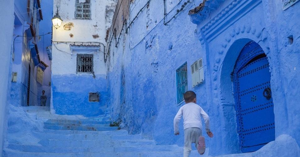 Menino corre em rua de Chefchaouen, Marrocos. Localizada nas montanhas Rif, no norte do país, Chefchaouen abriga casas e lojas com paredes pintadas em diferentes tons de azul