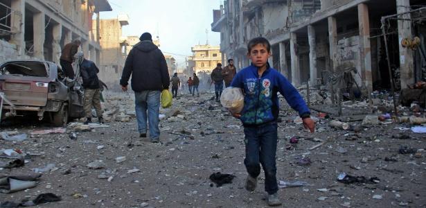 Garoto caminha em região destruída por ataque aéreo das forças do governo, em Binnish, na Síria