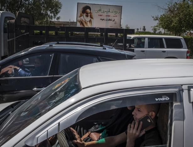 4.jun.2017 - Motoristas enfrentam engarrafamento próximo a propaganda do antigo líder espiritual iraniano aiatolá Khomeini, em Diyala, no Iraque