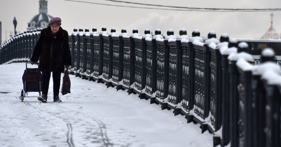 5.jan.2018 - Moradora caminha por ponte coberta de neve em Moscou, Rússia