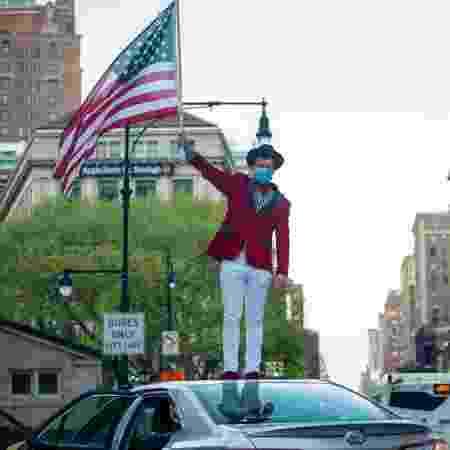 10.mai.2020 - Coronavírus: de máscara, homem agita bandeira dos EUA durante homenagem a profissionais de saúde em Nova York - Alexi Rosenfeld/Getty Images