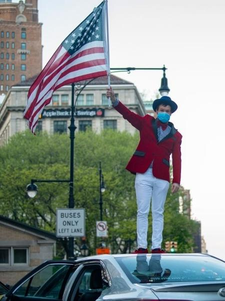 De máscara, homem agita bandeira dos EUA - Alexi Rosenfeld/Getty Images