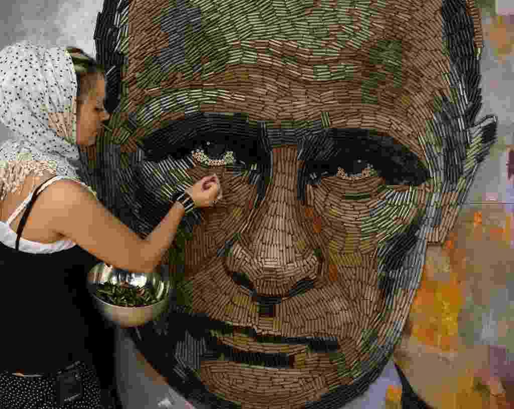 """27.jul.2015 - A artista Dariya Marchenko trabalha no retrato do presidente russo, Vladimir Putin, chamado de """"The Face of War"""" (a face da guerra, em tradução livre do inglês), feito com 5.000 cartuchos de balas trazidos da linha de frente do leste da Ucrânia, em seu estúdio localizado em Kiev. O retrato será apresentado juntamente com um romance que contará histórias de seis pessoas envolvidas no projeto, incluindo gente que ajudou a coletar os cartuchos. Marchenko considera sua arte filosófica, onde cada elemento tem um significado oculto. As obras feitas com cartuchos representam a vida do ser humano encerrada de forma brutal - Gleb Garanich/Reuters"""