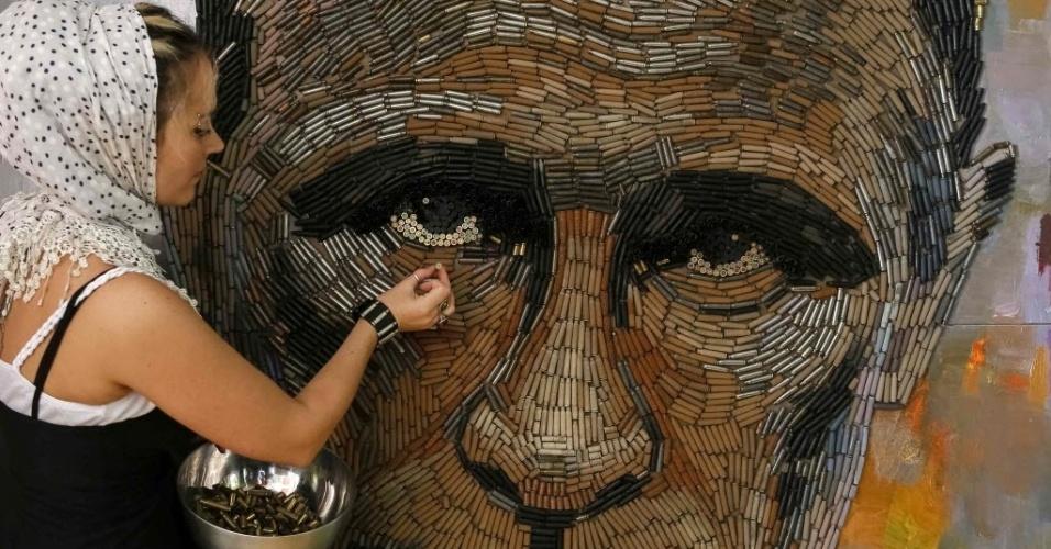 """27.jul.2015 - A artista Dariya Marchenko trabalha no retrato do presidente russo, Vladimir Putin, chamado de """"The Face of War"""" (a face da guerra, em tradução livre do inglês), feito com 5.000 cartuchos de balas trazidos da linha de frente do leste da Ucrânia, em seu estúdio localizado em Kiev. O retrato será apresentado juntamente com um romance que contará histórias de seis pessoas envolvidas no projeto, incluindo gente que ajudou a coletar os cartuchos. Marchenko considera sua arte filosófica, onde cada elemento tem um significado oculto. As obras feitas com cartuchos representam a vida do ser humano encerrada de forma brutal"""