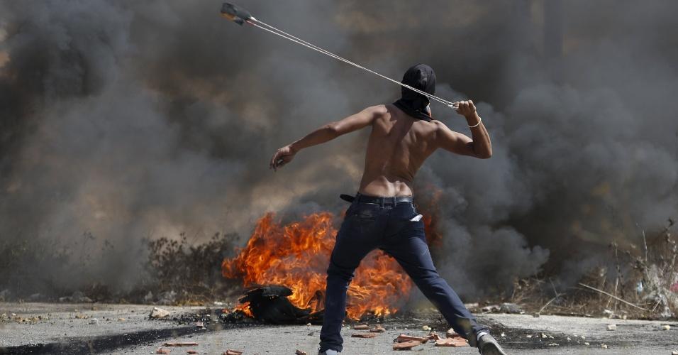5.out.2015 - Manifestante palestino usa arma de arremesso para atirar pedras contra militares israelenses perto do assentamento judeu de Bet El, próximo à cidade de Ramallah, na Cisjordânia. Assim como Jerusalém, a região tem vivido uma escalada de confrontos nas ruas após o assassinato de quatro israelenses por palestinos e a morte de dois jovens palestinos por tropas de Israel