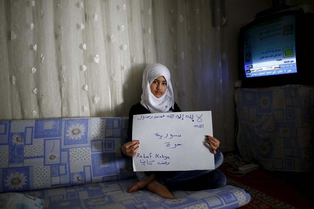 A refugiada síria Rahaf Kahya, 13, segura um cartaz que diz: