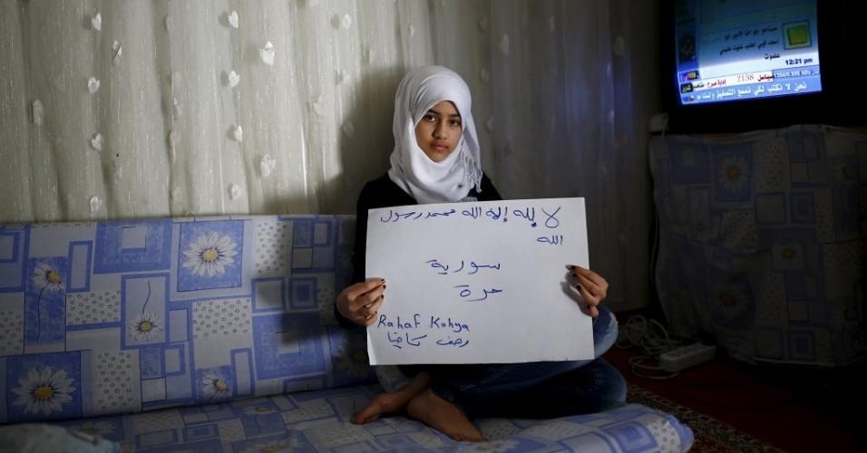 """A refugiada síria Rahaf Kahya, 13, segura um cartaz que diz: """"Não há nenhum deus senão Alá e Maomé é o mensageiro de Alá. Síria livre"""". Ela vive no campo de refugiados de Nizip, na província de Gaziantep, na Turquia. A guerra civil na Síria, que já deixou centenas de milhares de mortos, empurra outros tantos para o exílio, entre muitos deles crianças. Os desenhos das crianças do acampamento mostram memórias de suas casas, traumas vividos e esperanças para o seu futuro. Dos 2,3 milhões de refugiados sírios que vivem na Turquia, mais da metade são crianças"""