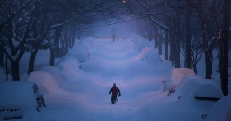 24.jan.2016 - Um garoto não se importa com a tempestade de neve e corre por uma rua para brincar na cidade de Washington, nos Estados Unidos, no último sábado (23). No município, são esperados 61 centímetros de neve no fim de semana