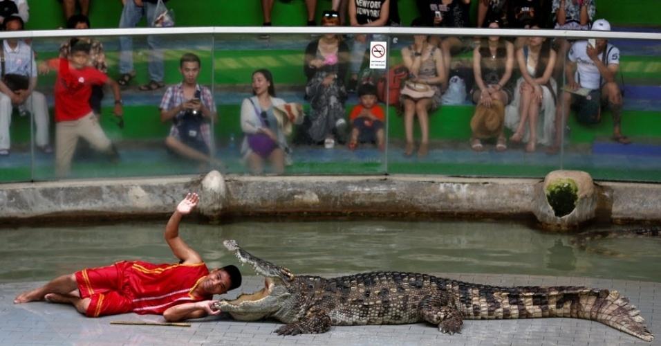 7.jun.2016 - Um tratador sorri ao colocar a cabeça dentro da boca de um crocodilo durante um show para turistas em um zoológico na província de Chonburi, Tailândia