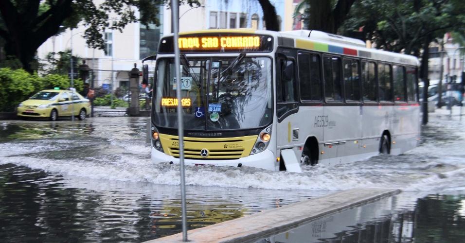 20.set.2016 - Choveu forte no Rio de Janeiro durante a madrugada desta terça-feira (20), o que provocou problemas em vários bairros, como alagamentos, bolsões d'água e queda de luz. Na imagem, ônibus atravessa bolsão d'água na rua do Passeio, no centro da capital fluminense