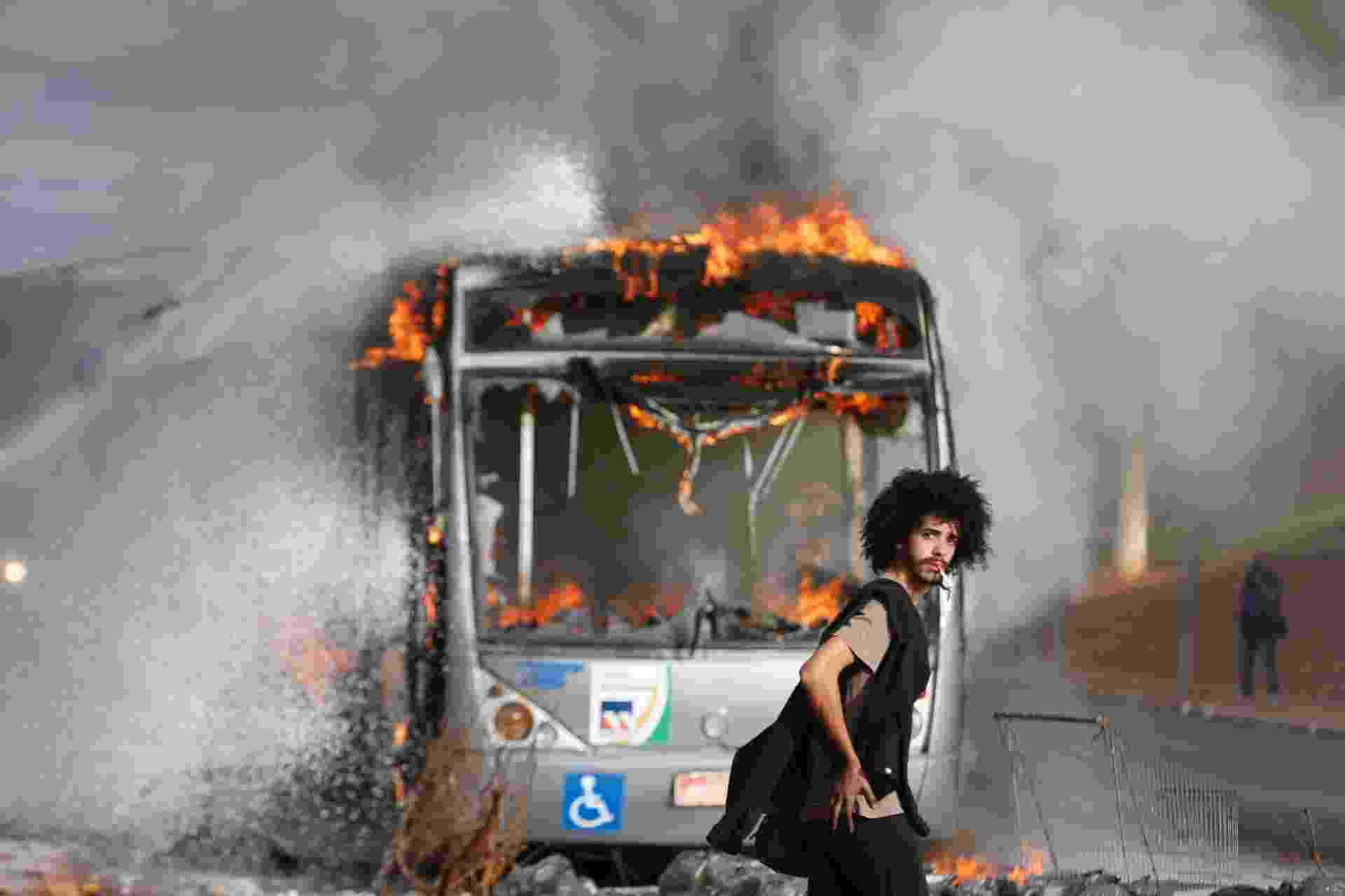 13.dez.2016 - Jovem passa diante de ônibus incendiado durante protesto na Esplanada dos Ministérios, em Brasília, contra a PEC 55, que prevê um teto de gastos para o governo federal durante 20 anos - Pedro Ladeira/Folhapress