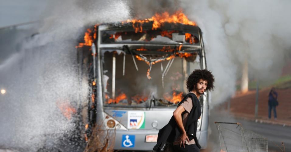 13.dez.2016 - Jovem passa diante de ônibus incendiado durante protesto na Esplanada dos Ministérios, em Brasília, contra a PEC 55, que prevê um teto de gastos para o governo federal durante 20 anos