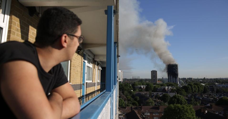 14.jun.2017 - Rapaz assiste de seu prédio ao incêndio na Grenfell Tower, no bairro de North Kensington, em Londres
