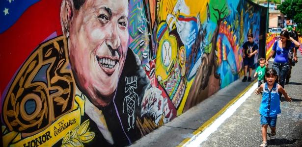 Crianças passam por mural com o rosto do presidente Hugo Chávez