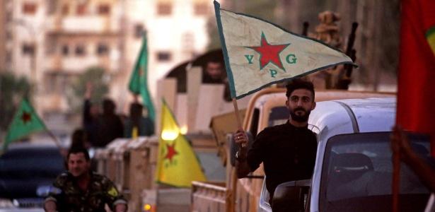 Apoiadores e soldados das Unidades de Proteção do Povo Curdo da Síria (YPG) dirigem na rua com bandeiras de Qamishli para celebrar o anúncio das Forças Democráticas da Síria (SDF) que disse ter tomado o controle total de Raqqa do Estado islâmico - DELIL SOULEIMAN/AFP