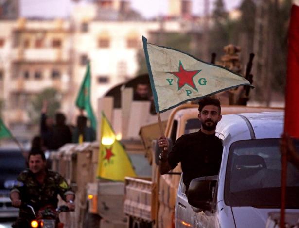 Apoiadores e soldados das Unidades de Proteção do Povo Curdo da Síria (YPG) dirigem na rua com bandeiras de Qamishli para celebrar o anúncio das Forças Democráticas da Síria (SDF) que disse ter tomado o controle total de Raqqa do Estado islâmico