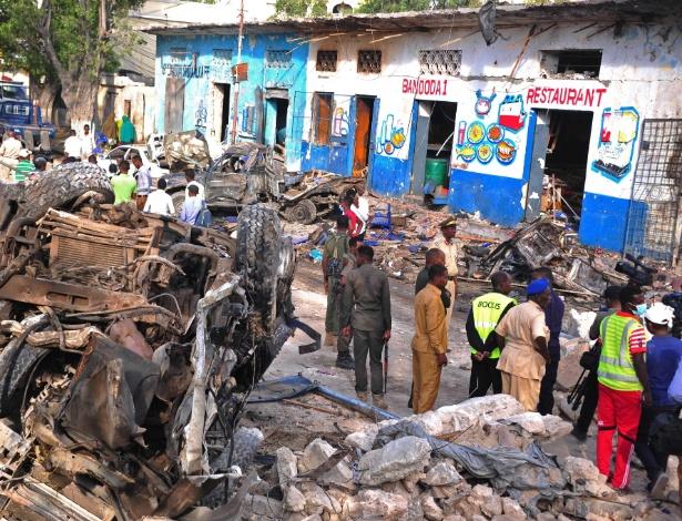 29.out.2017 - Habitantes da cidade de Mogadíscio observam destroços na rua após explosão de carro bomba