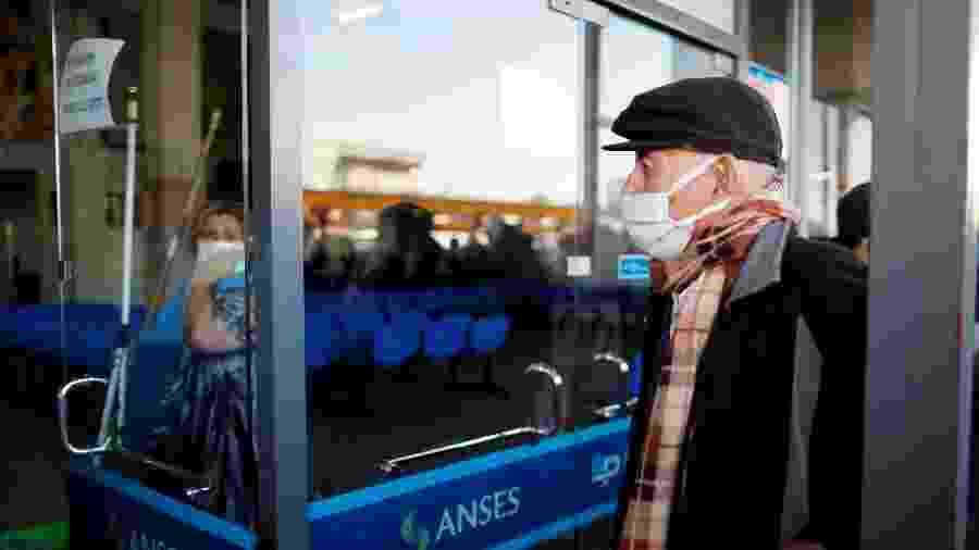 03.abr.2020 -  Idoso em frente a um banco, aberto pela primeira vez desde a quarentena obrigatória em Buenos Aires, na Argentina - Agustin Marcarian/Reuters